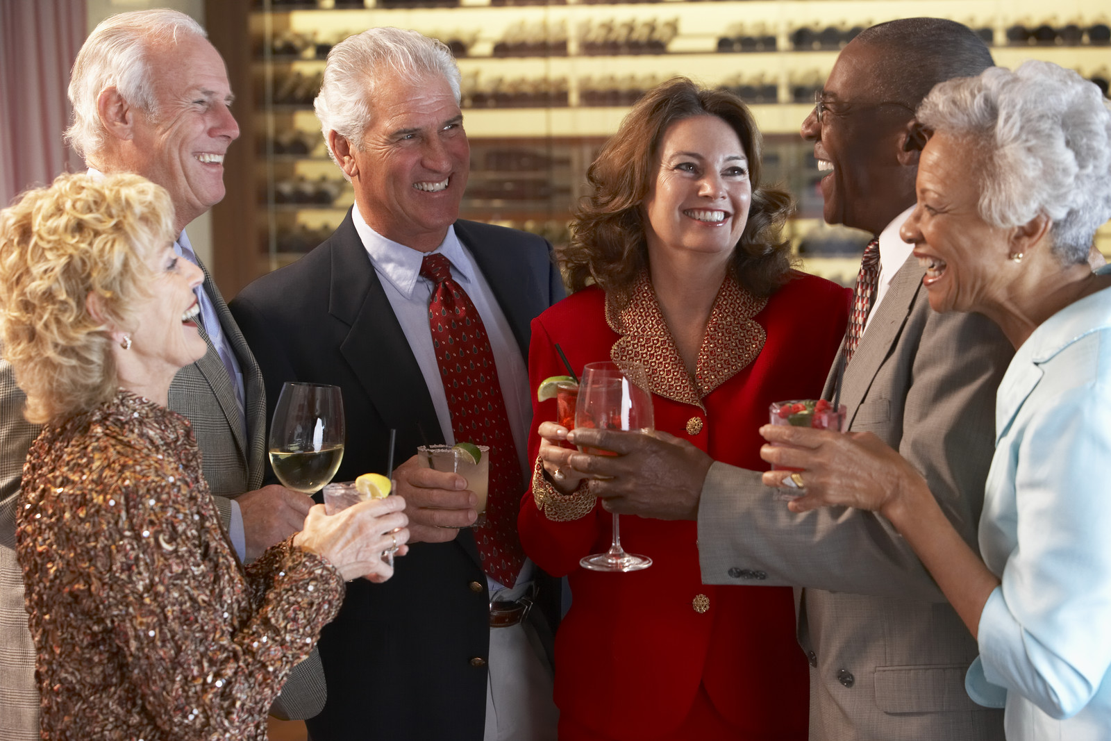 Six seniors standing in a bar holding glasses of wine talking and smiling