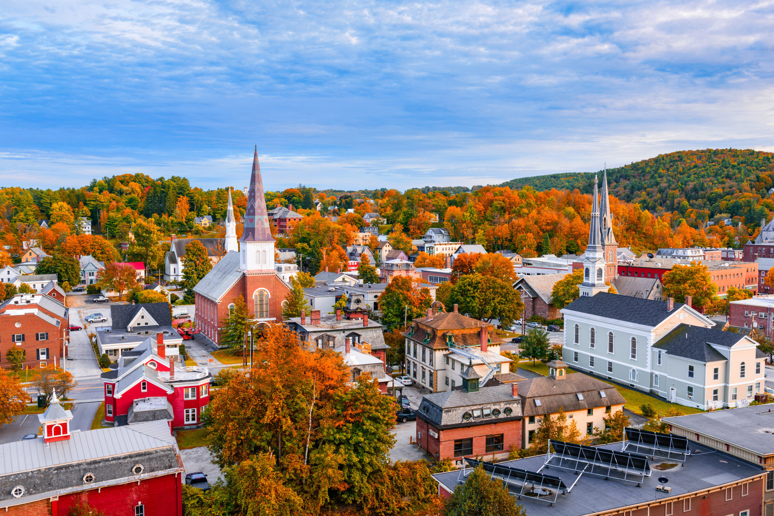 Small town cityscape with colonial style buildings and churches with tall spires, surrounded by fall colors and blue sky