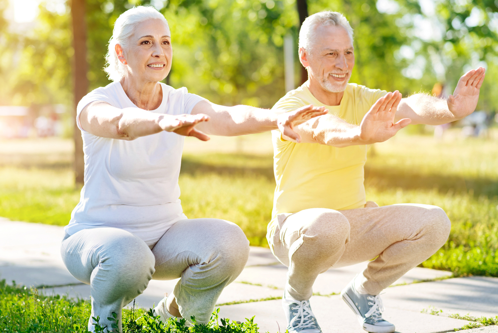 Two seniors in a park doing squats