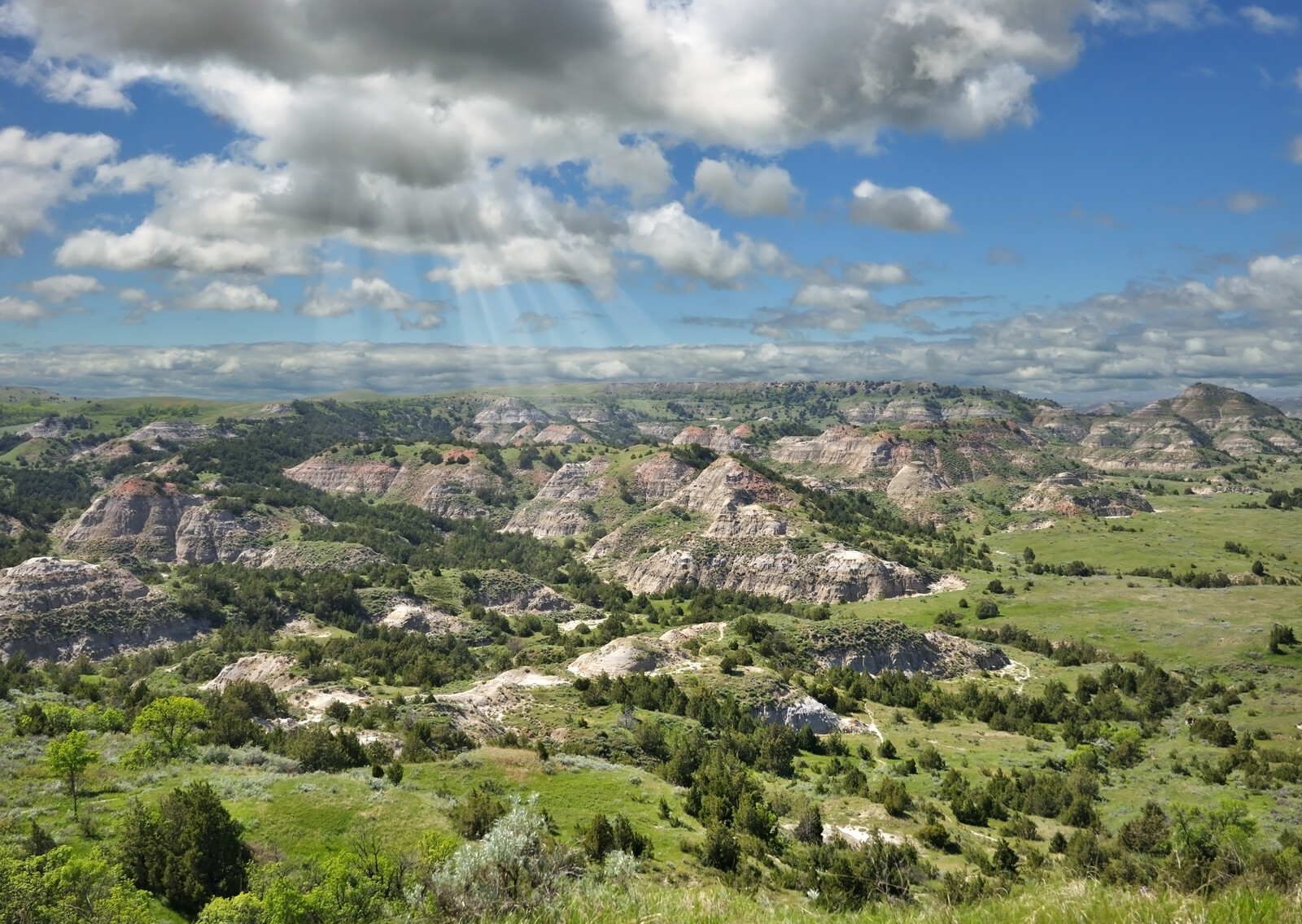 Best Places to retire in North Dakota - Summer mountain landscape of painted canyon in north dakota with blue skies and puffy white clouds, with sun beams shining down on the mountain tops