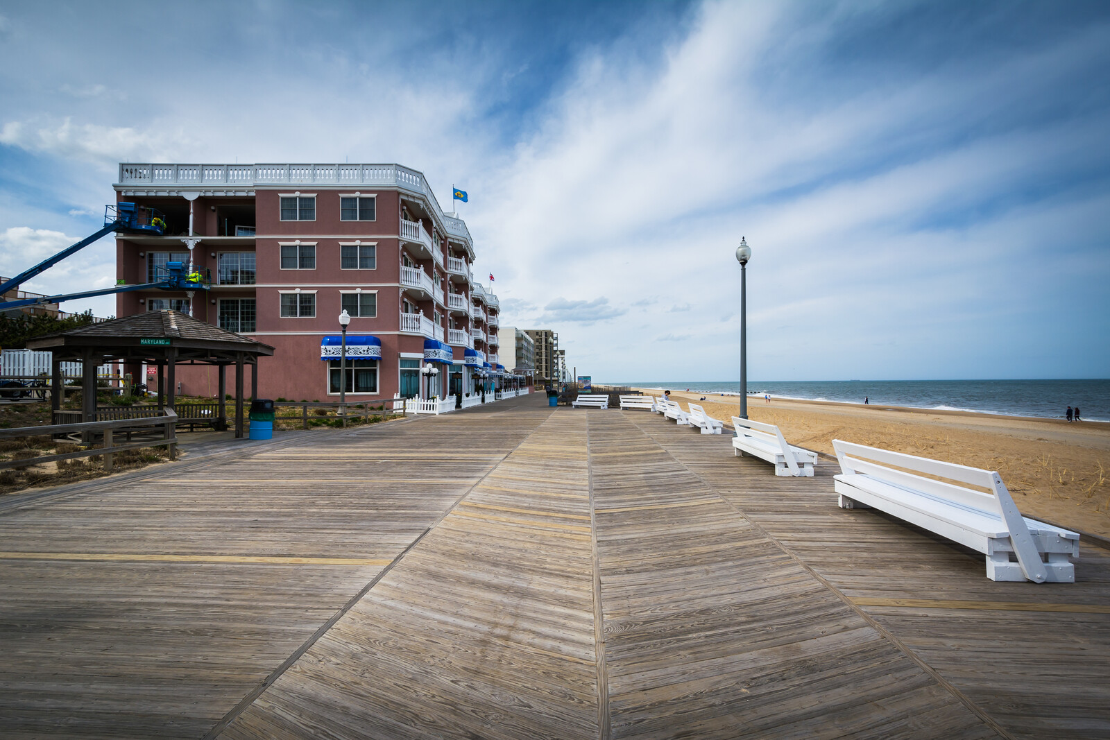 Boardwalk in Rehoboth Beach with a hotel on the left and white benches lining the boardwalk and beach and ocean on the right during offseason, beautiful blue skies.