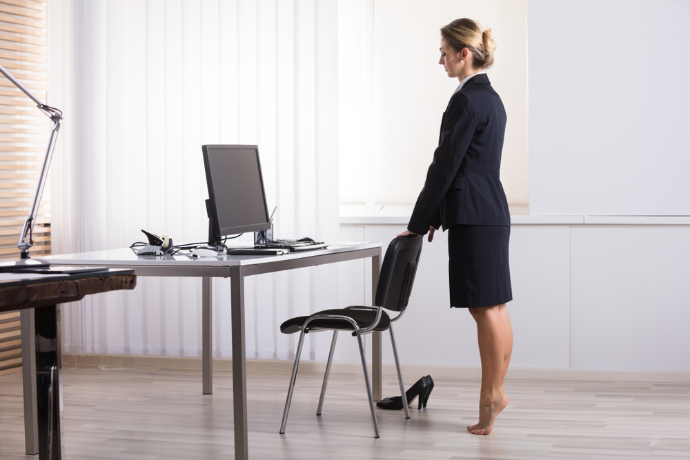 A business woman doing toe stretches in the office