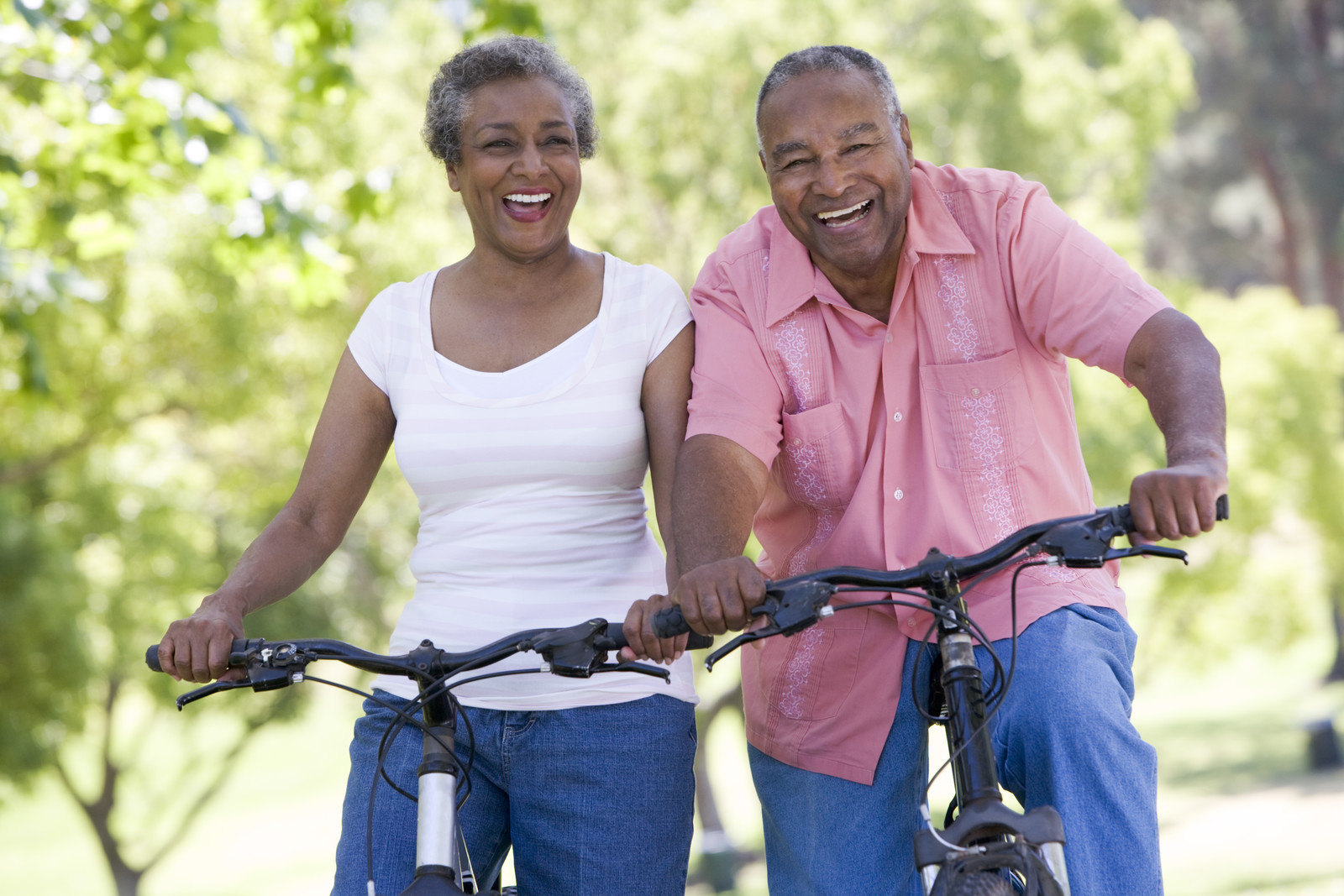 A senior couple smiling riding bikes outside on a sunny day