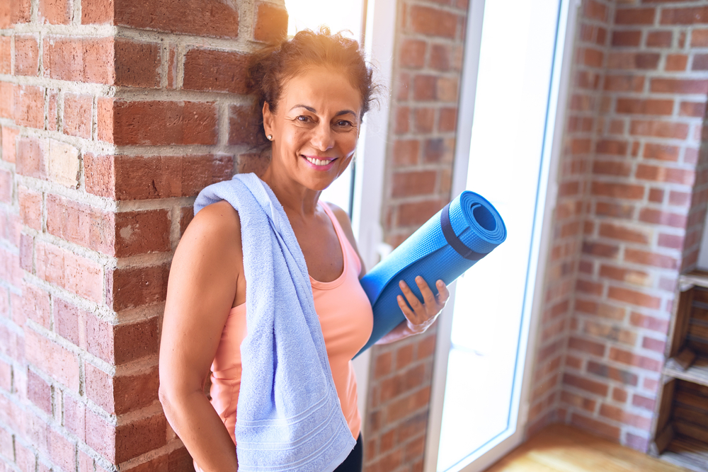 A middle aged woman in exercise gear next to a wall