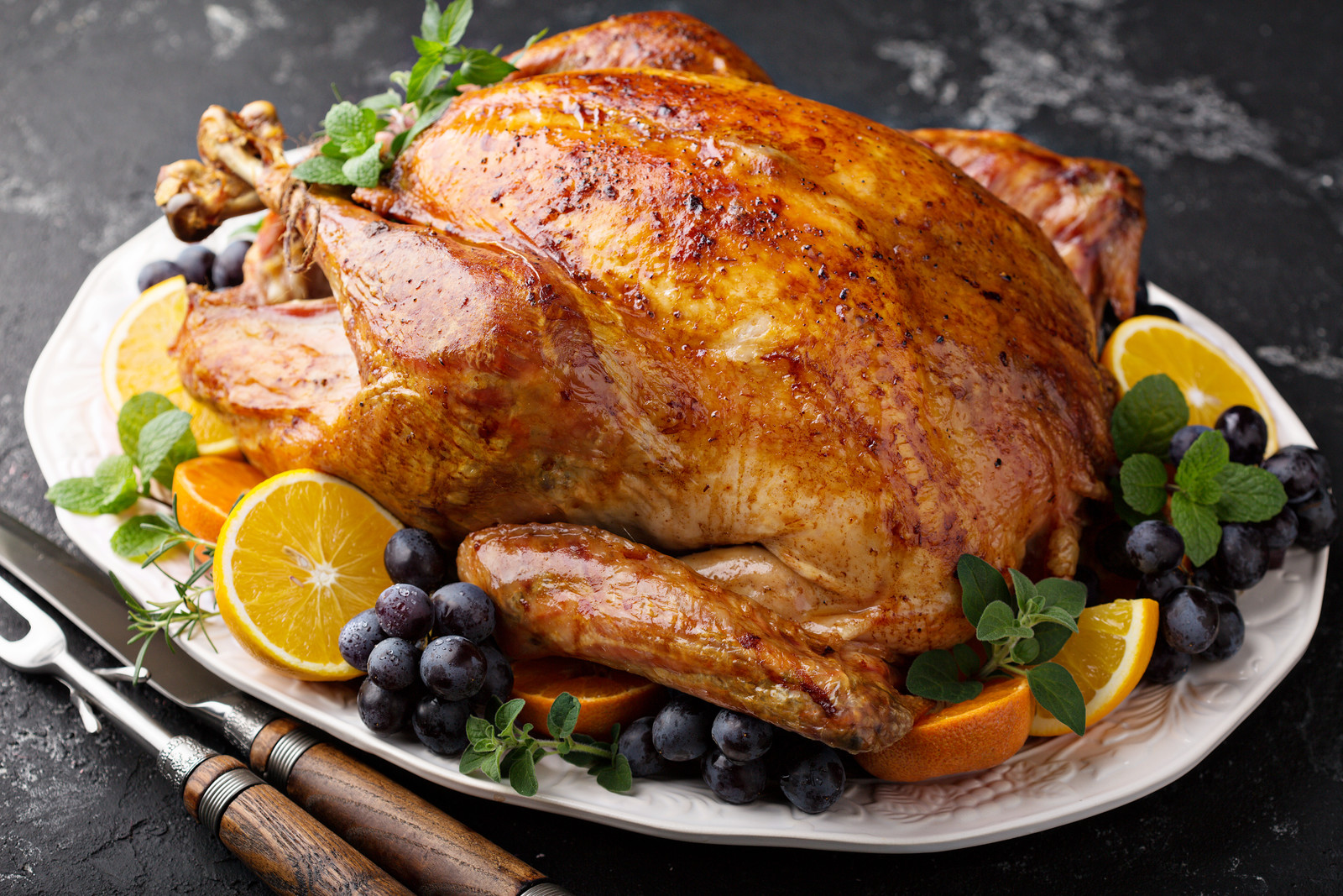 Whole roasted turkey on white platter garnaished with fresh oregano leaves, grapes, fresh mint sprigs and orange slices sitting on a marble table witha  serving knife and fork resting on the side