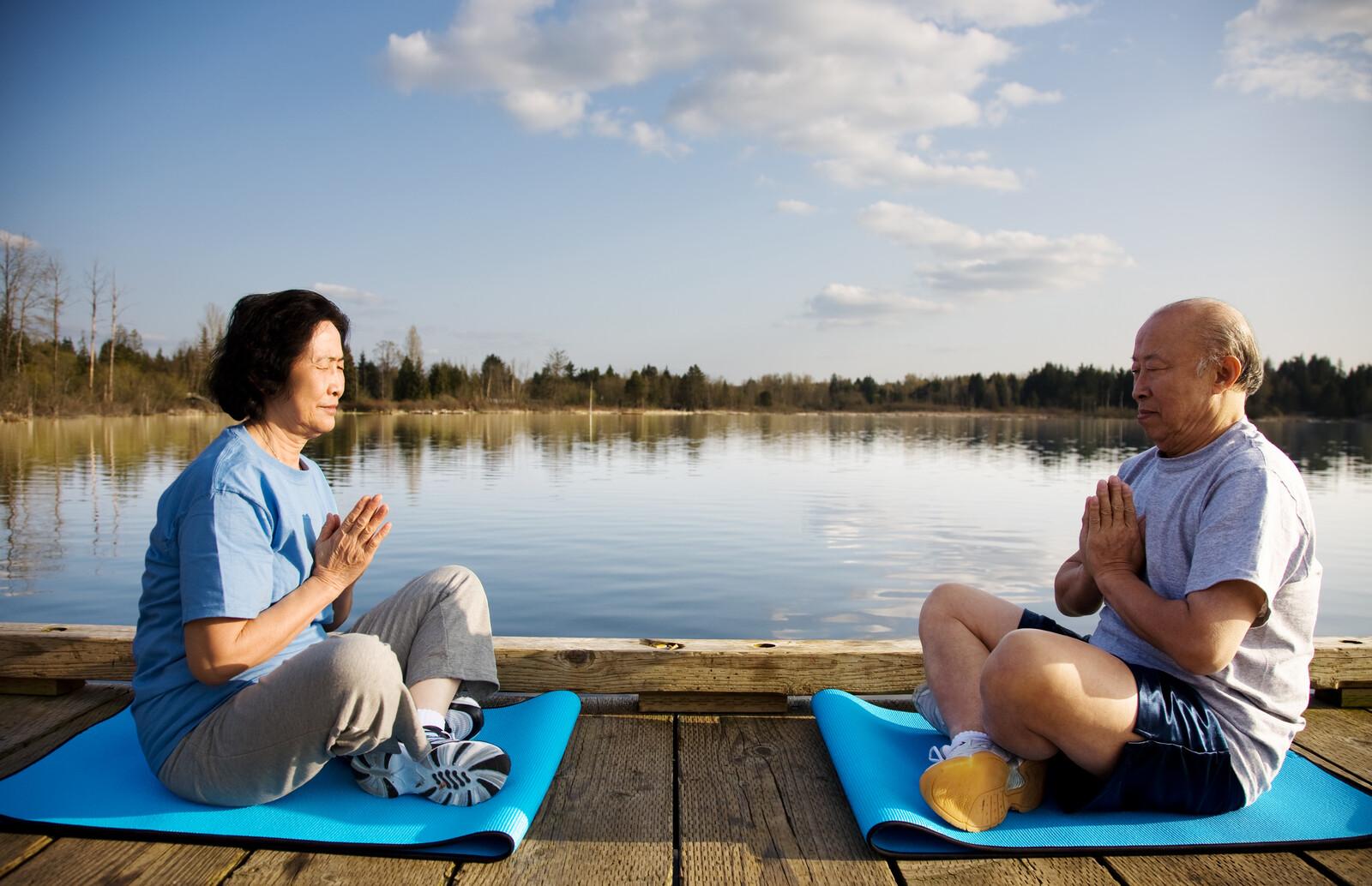 senior couple meditating on yoga mats on a dock over a lake