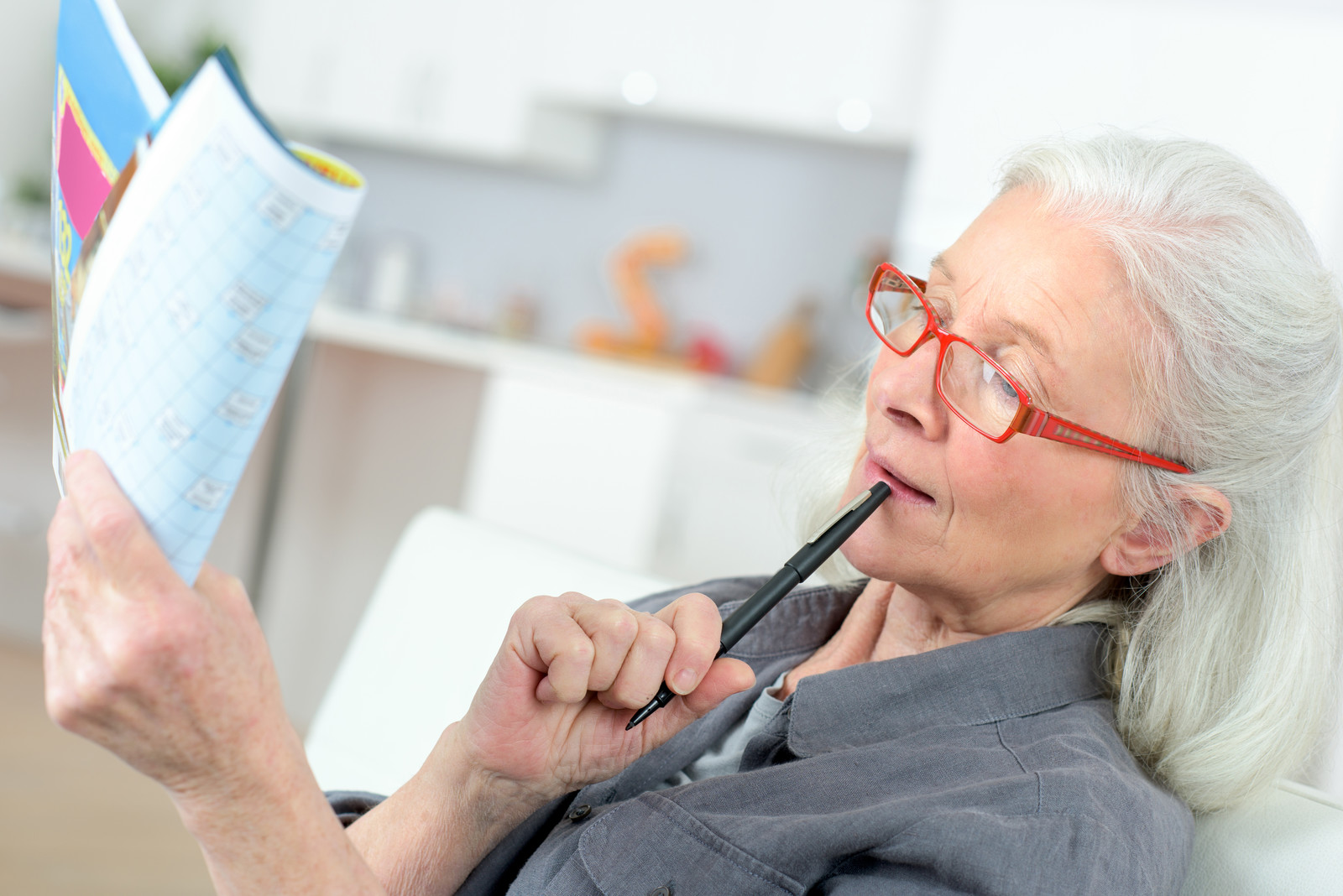 senior woman working on a crossword puzzle