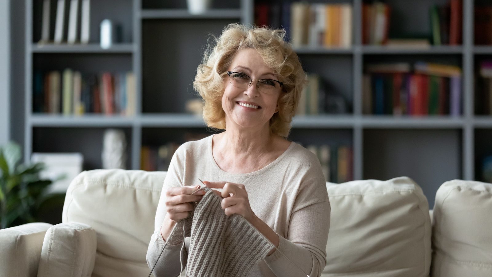 Happy senior woman sitting on the couch knitting
