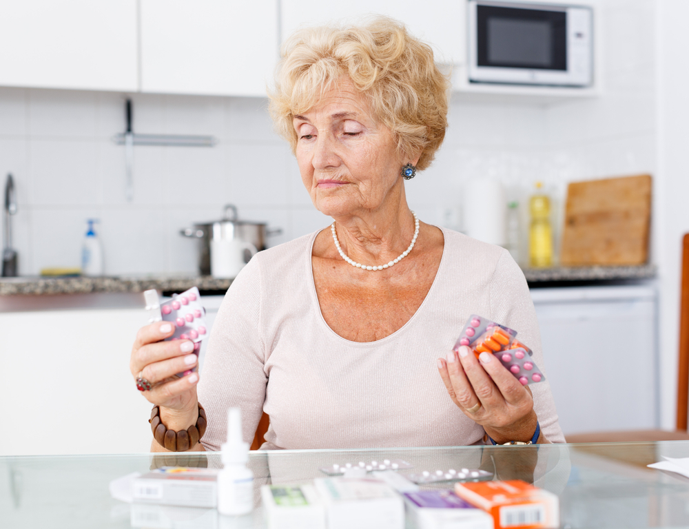 A senior woman looking at medication while sitting in her kitchen