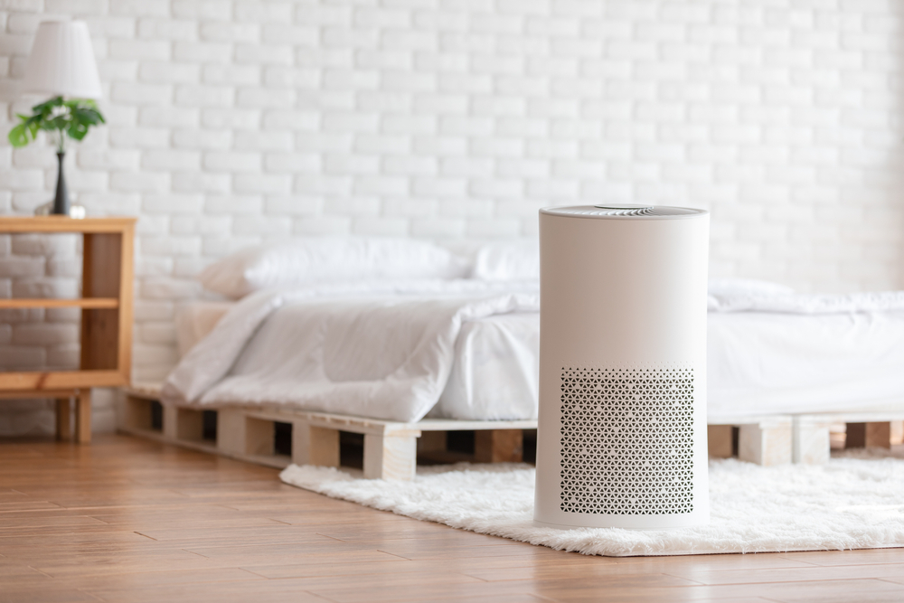 An air purifier in someone's bedroom, in front of a bed and a white brick wall