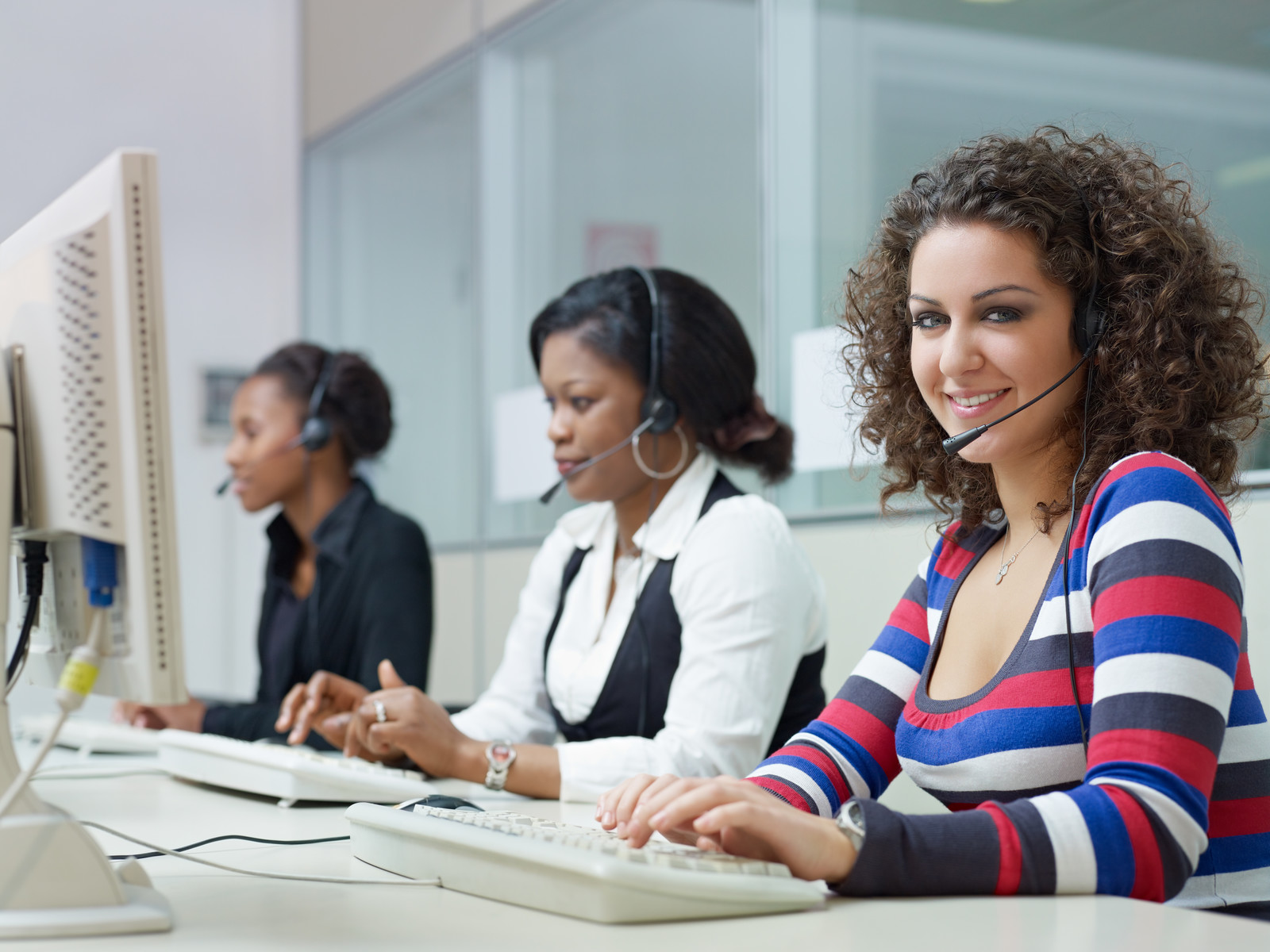 Call center with three women on their headsets sitting at computers representing navigators helping people choose insurance