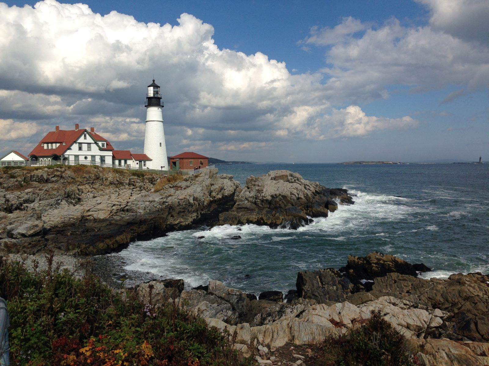 Places To Retire in Maine - Lighthouse on the shoreline of Maine blue skies with white billowy clouds and waves hitting the rocky shores