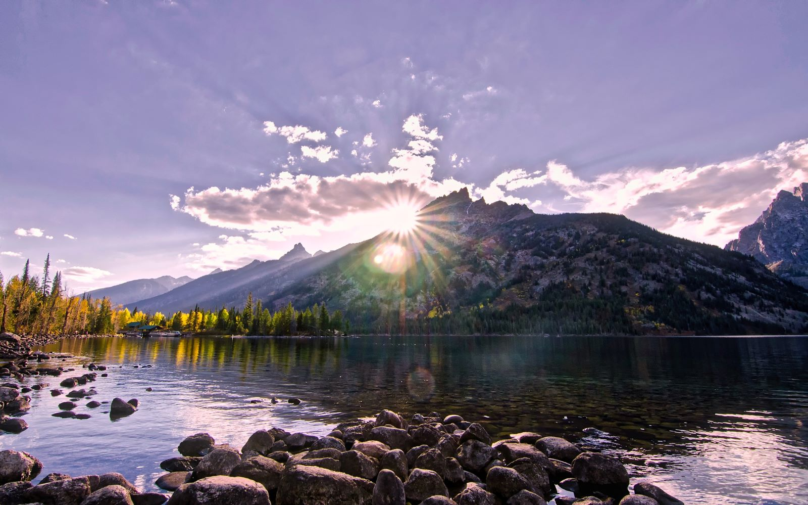 Places To Retire in Wyoming-Sun peaking over the mountains, over a clear lake with pine trees along the shore with blue skies