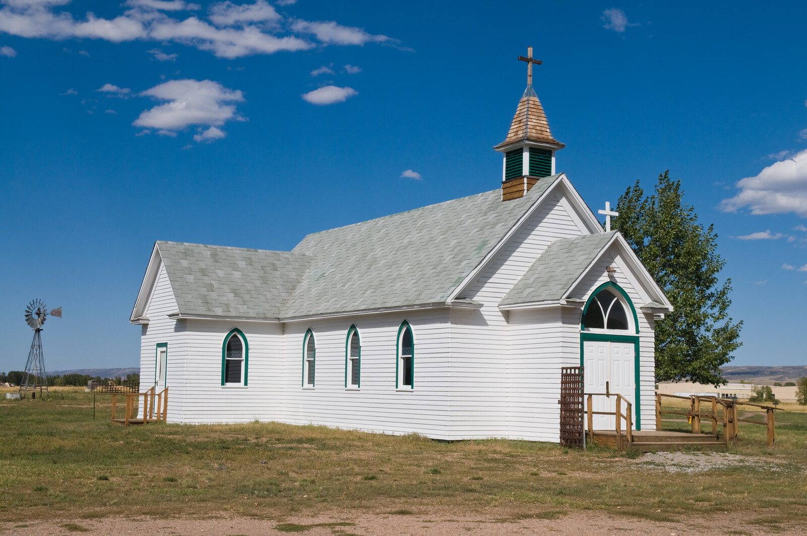 White Historic church in Laramie with a  windmill in the background, blue skies and a tree in the background