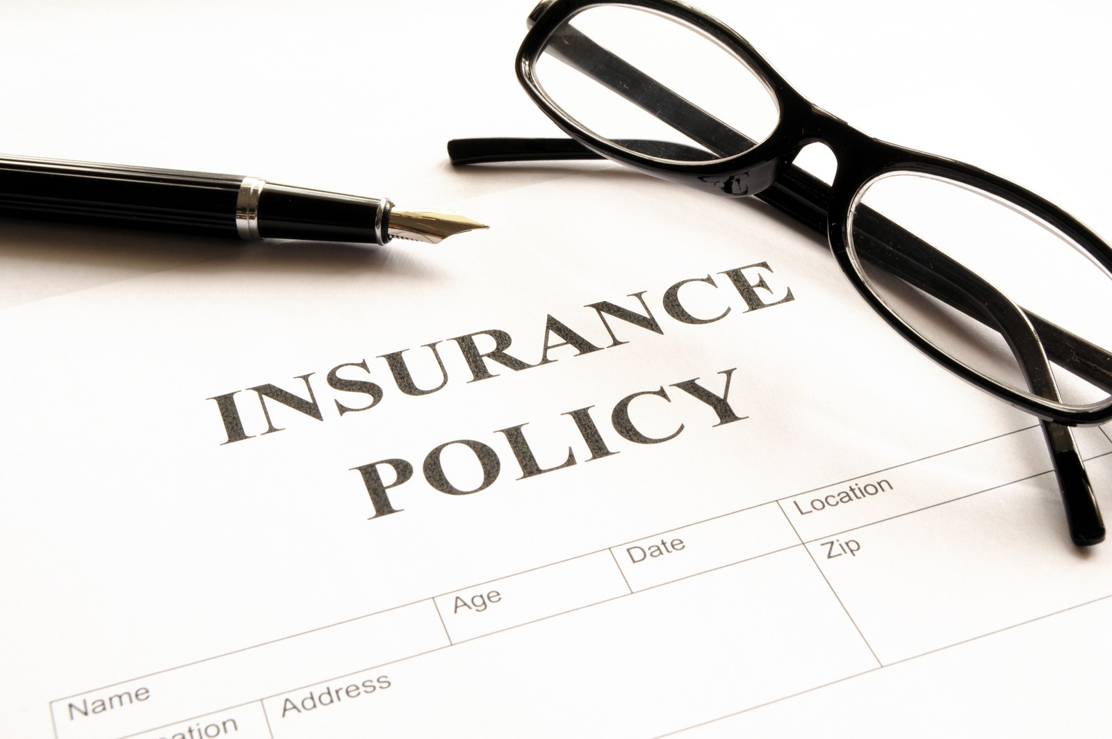 Insurance Scams  -  Insurance policy form with reading glasses sitting on top with a pen