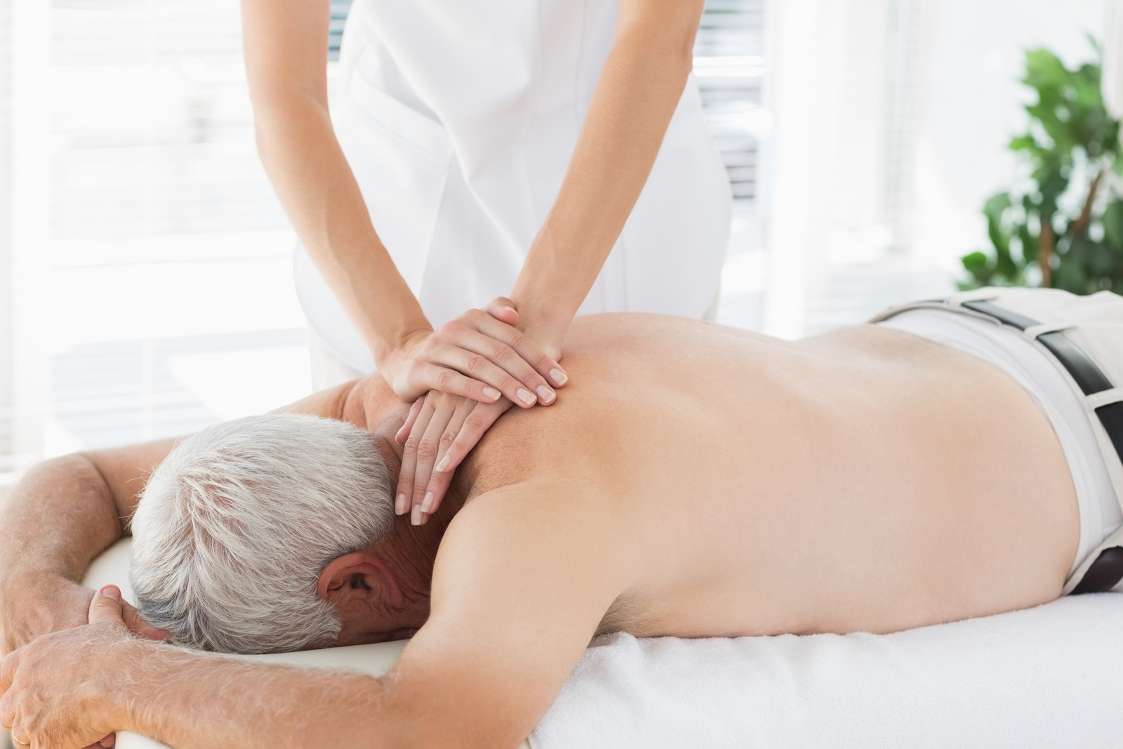 Senior man laying face down on a massage table receiving a massage, using pressure around the neck and shoulders