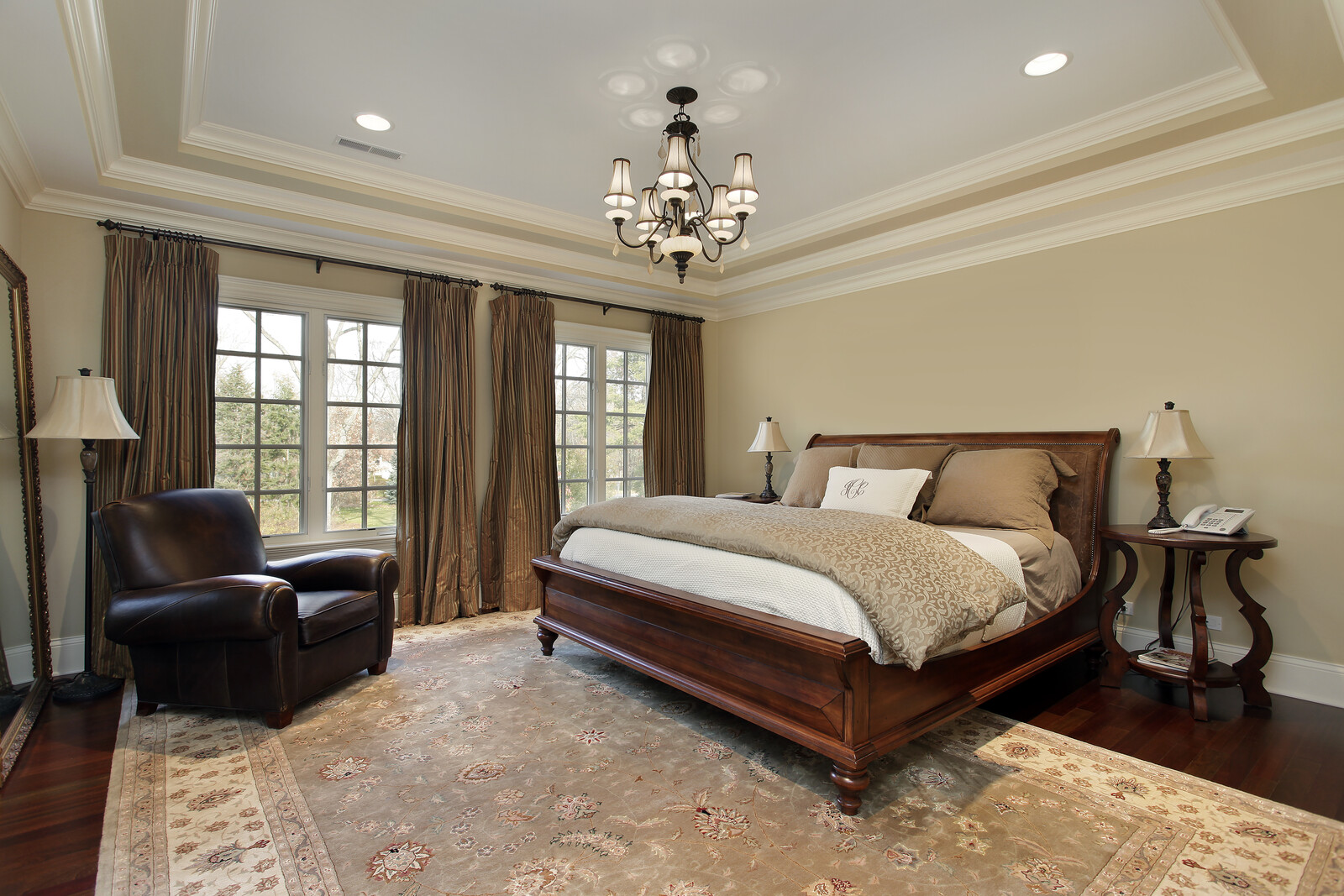 Elegant bedroom with sleigh bed and large windows with nightstands with lamps and a telephone