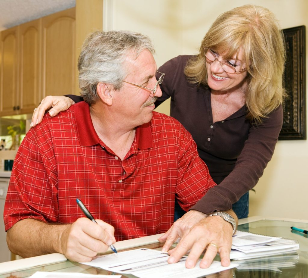 Senior couple smiling as they pay off their bills
