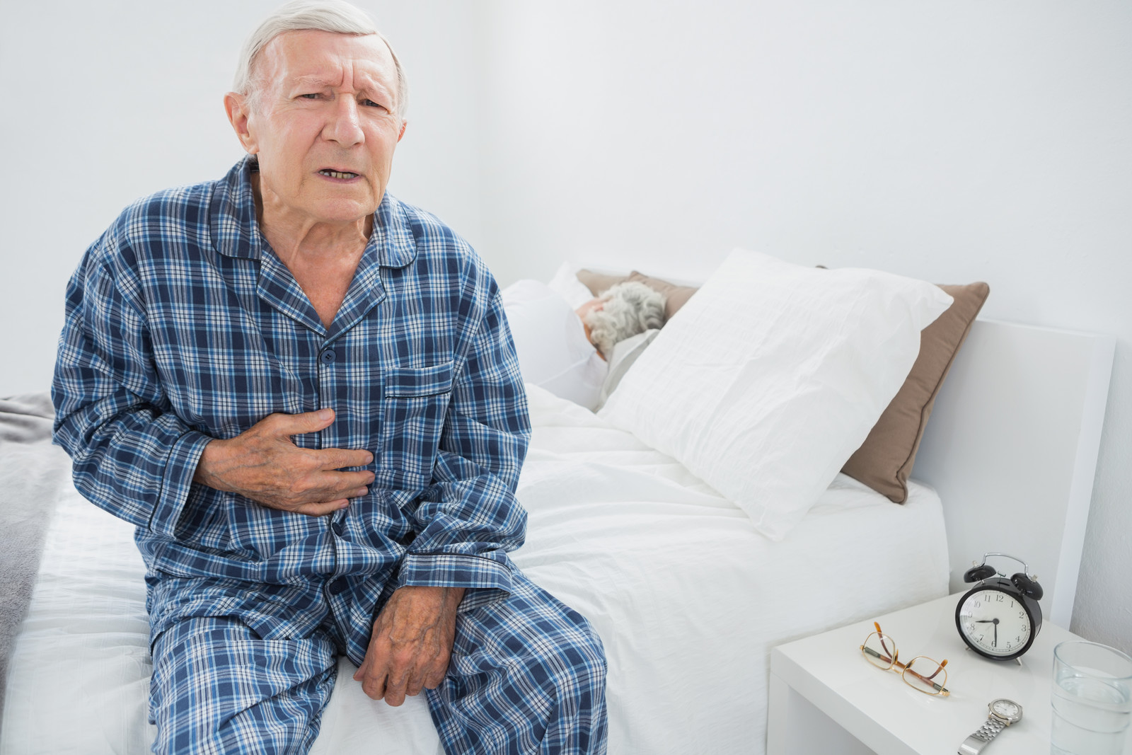 Senior man in blue pajamas holding his abdomen sitting ont he side of his bed