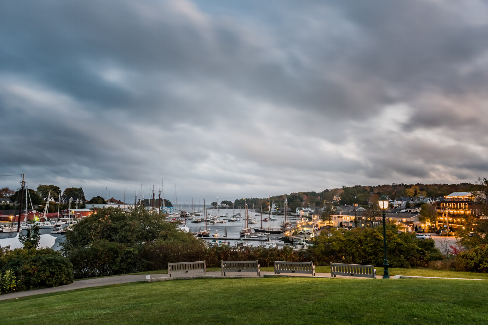 Sunset overlooking Camden Maine - Cloudy sky with boats in the harbor and evening lights on the local businesses
