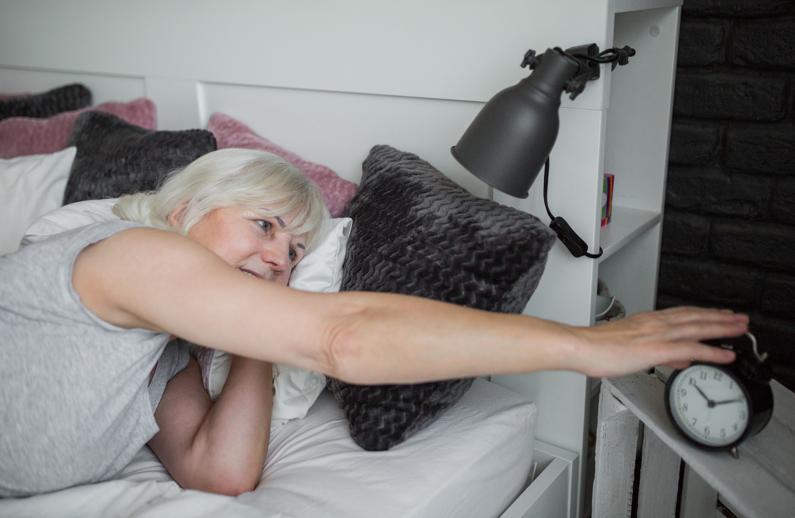 Senior woman reaching over to her alarm clock in the morning