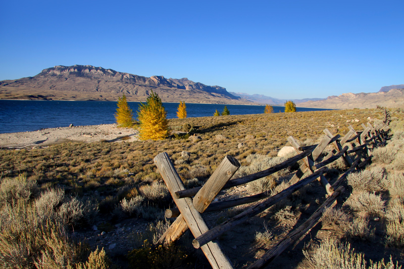 Cody resevoir with hills in the background and blue skies with a wood fence lining the lake