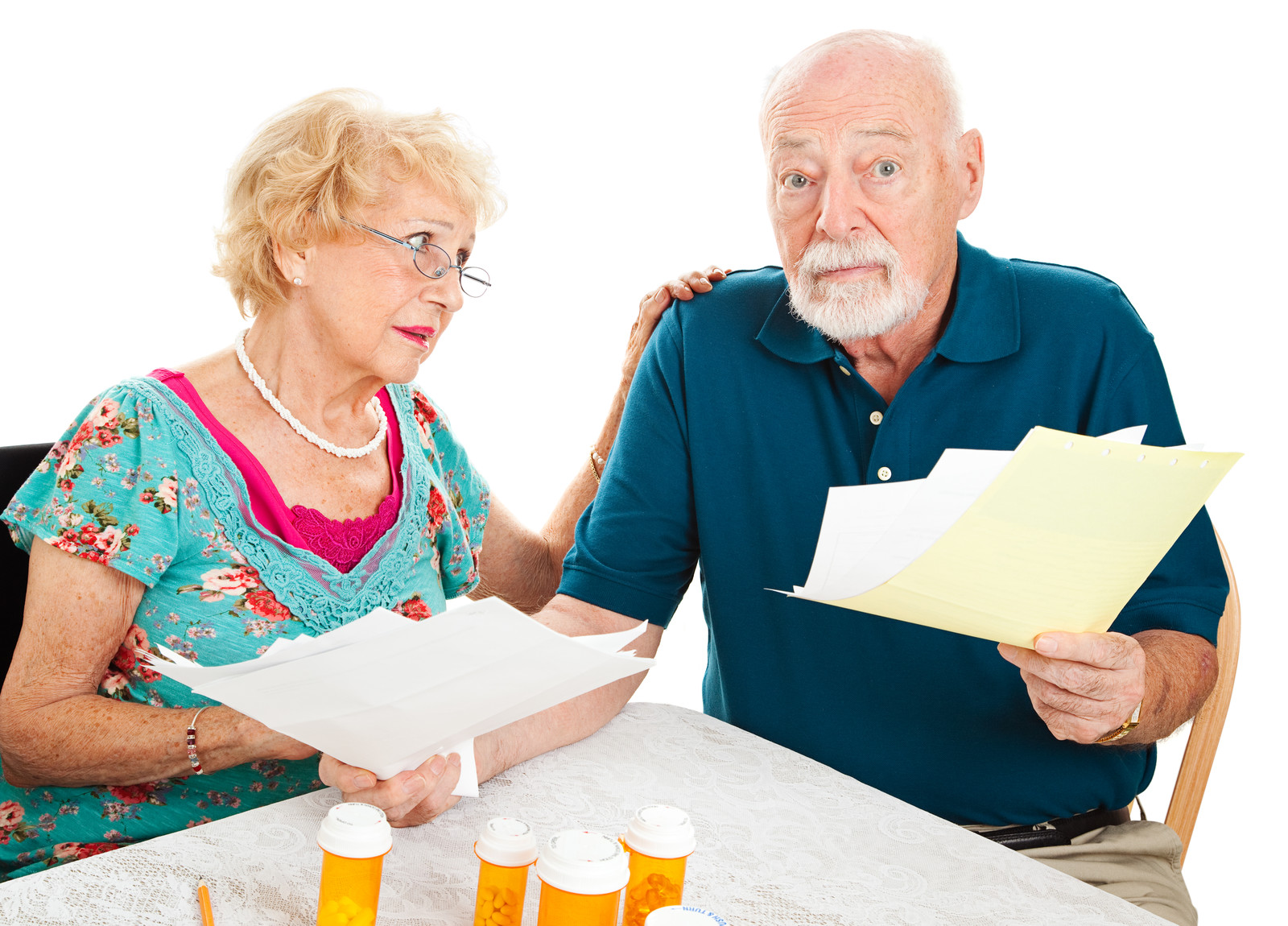 Senior Couple stressed By Medical Bills sitting at kitchen table, with pill bottles on table