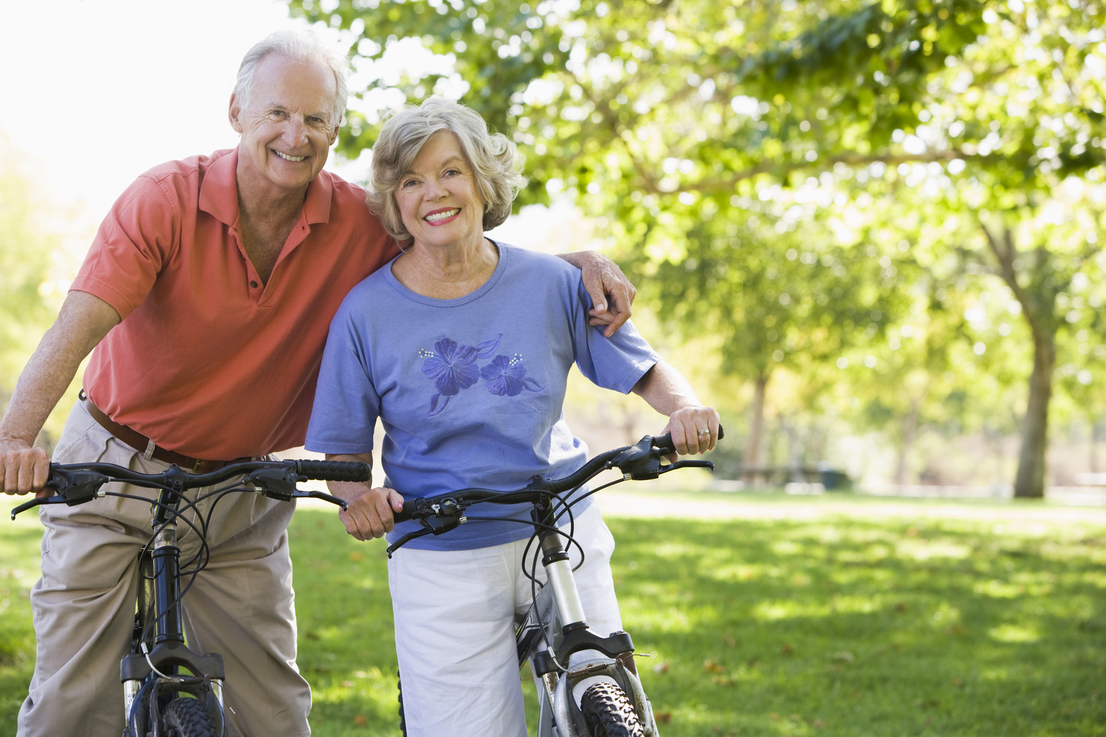 Senior couple on a sunny day in the park sitting on their bicycles