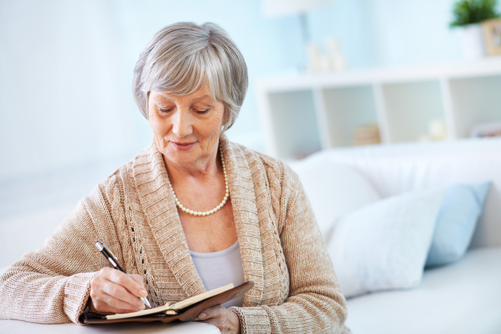 Senior woman writing notes in her bedroom