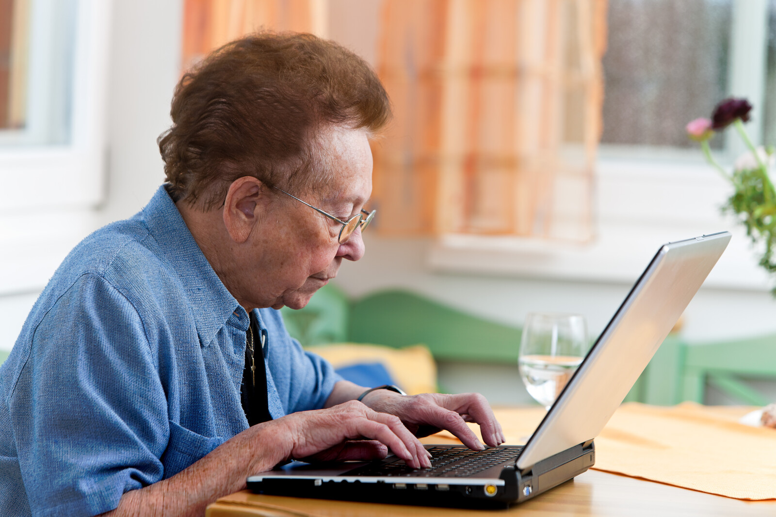Senior woman with a laptop writing an e-mail from home