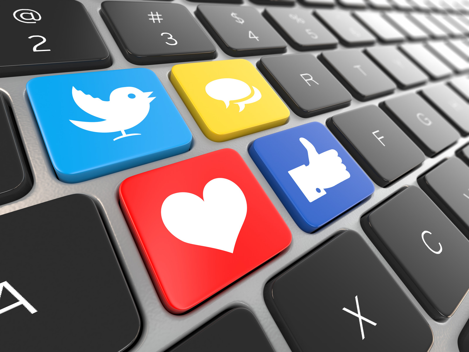 Laptop key board with four bright colored keys with a twitter symbol, the Love sympbol, a chat symbol, and a thumbs up All representing social media