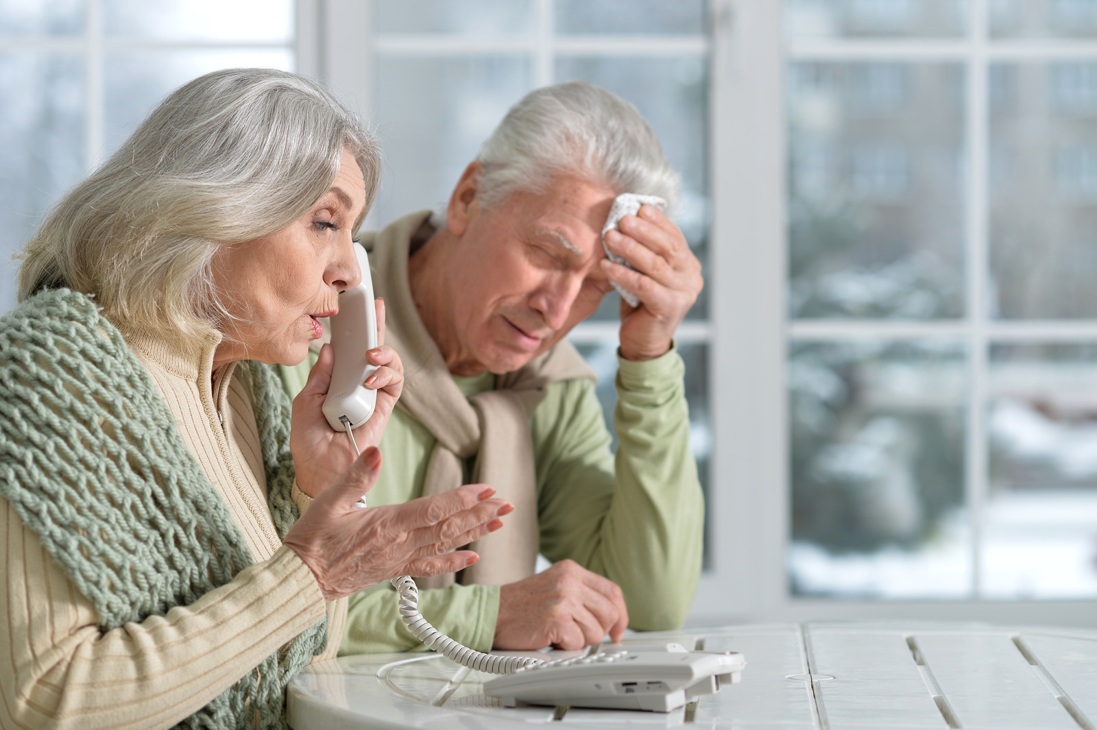 Top 10 Ways For Seniors To Relieve Stress - Senior woman looking distressed on the phone and her husband next to her with his hand to his forehead