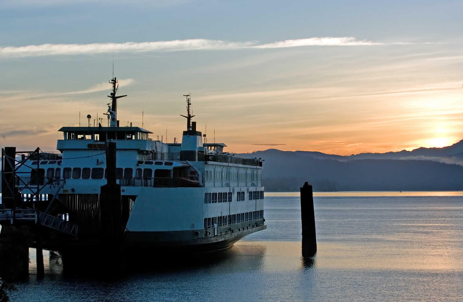 Large Ferry on the bay in Anacortes at sunset with the hills in the background and sunset reflecting off the water