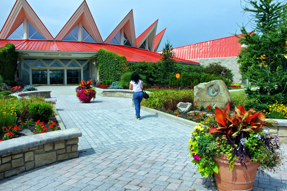The Tamarack center in Beckley West Virginia highlighting the red roof and a woman walking towards the center
