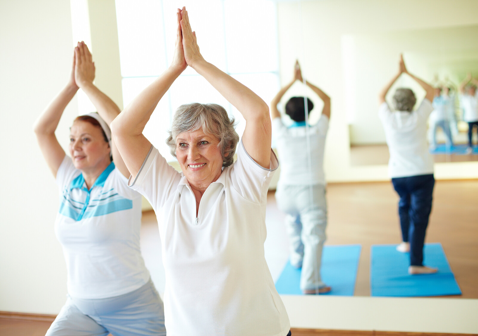 Two senior women in yoga class holding a pose while smiling