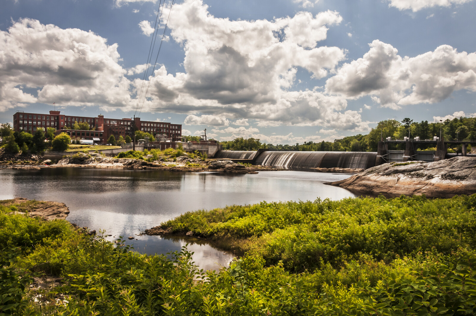 View of Fort Ambross Mill and Ambross Dam in the town of Brunswick in maine,  Blue skies sunny day with greenery lining the water