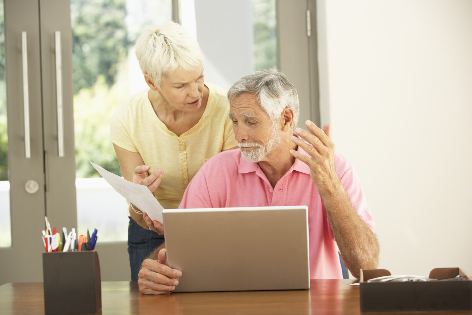 The photo represents a worried senior couple, the man is sitting in front of a laptop and his wife is standing next to him