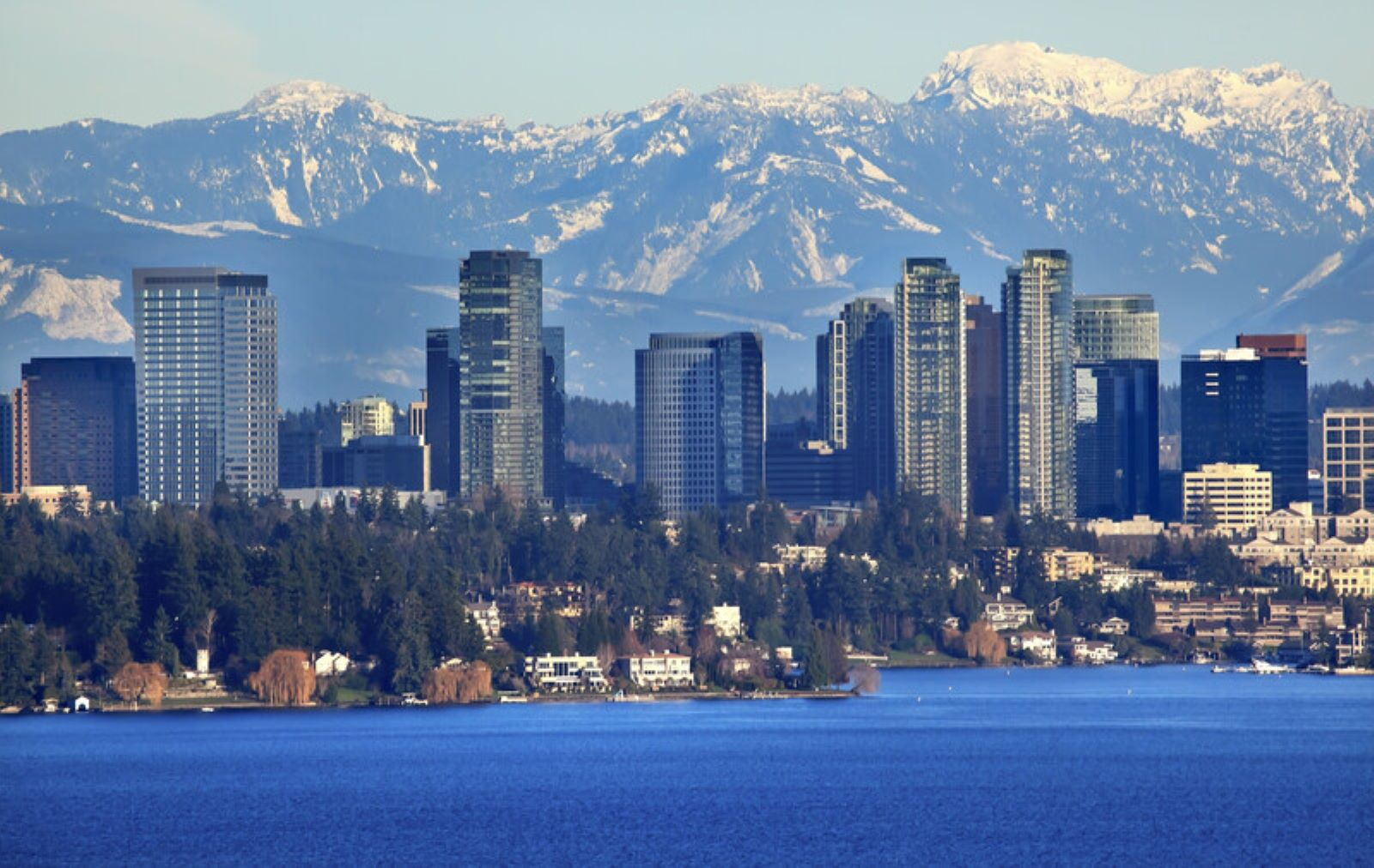 Bellevue City skyline with the Cascade Mountain Range in the back with blue skies in back and blue water in the front  of the city.