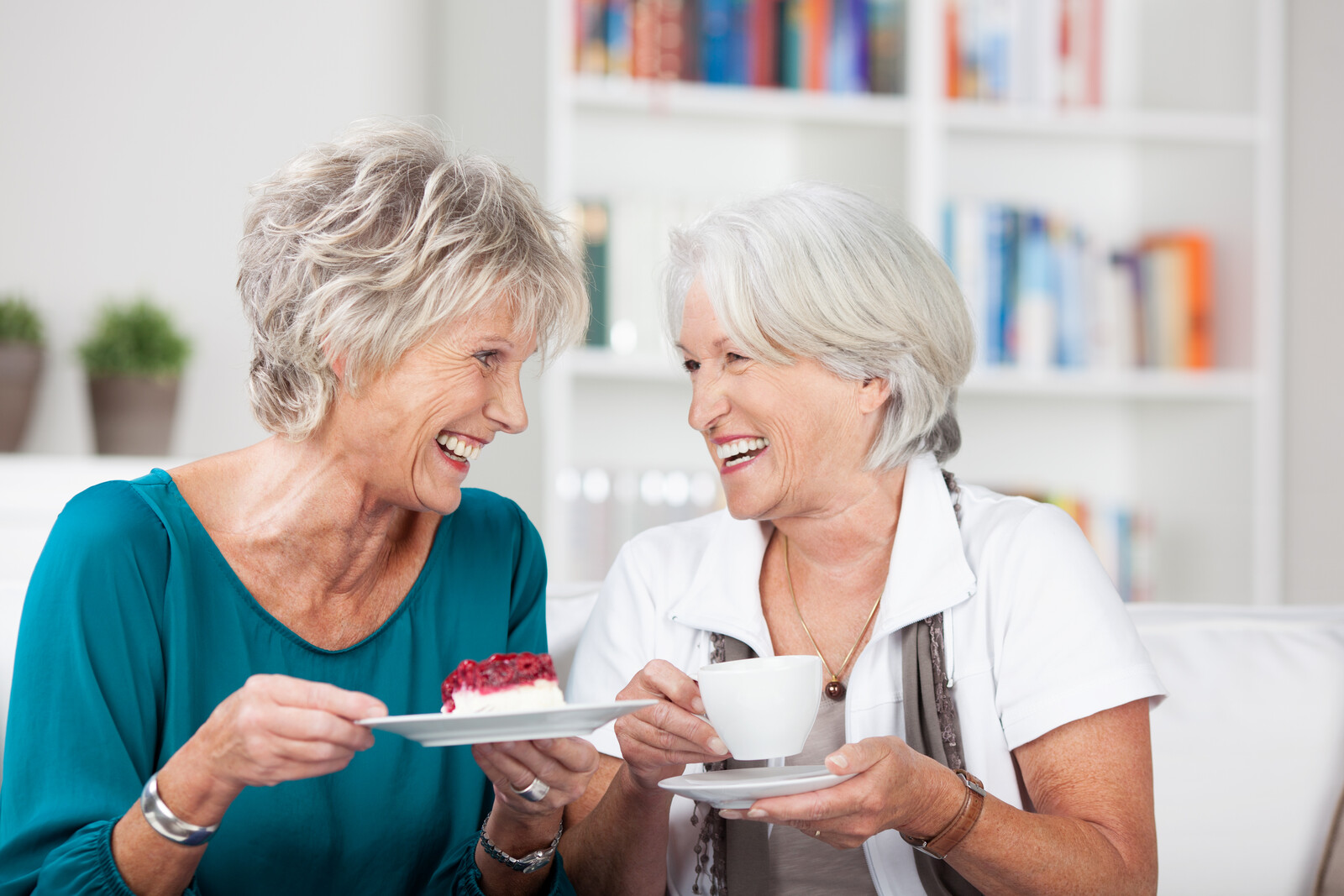 Two senior women sitting on a couch enjoying coffee and dessert laughing together