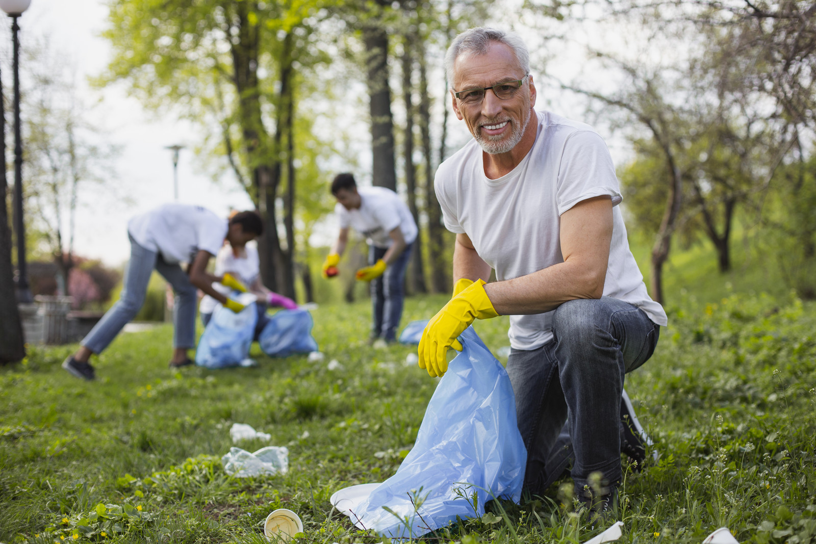 Senior man smiling looking into the camera as he picks up trash with other volunteers