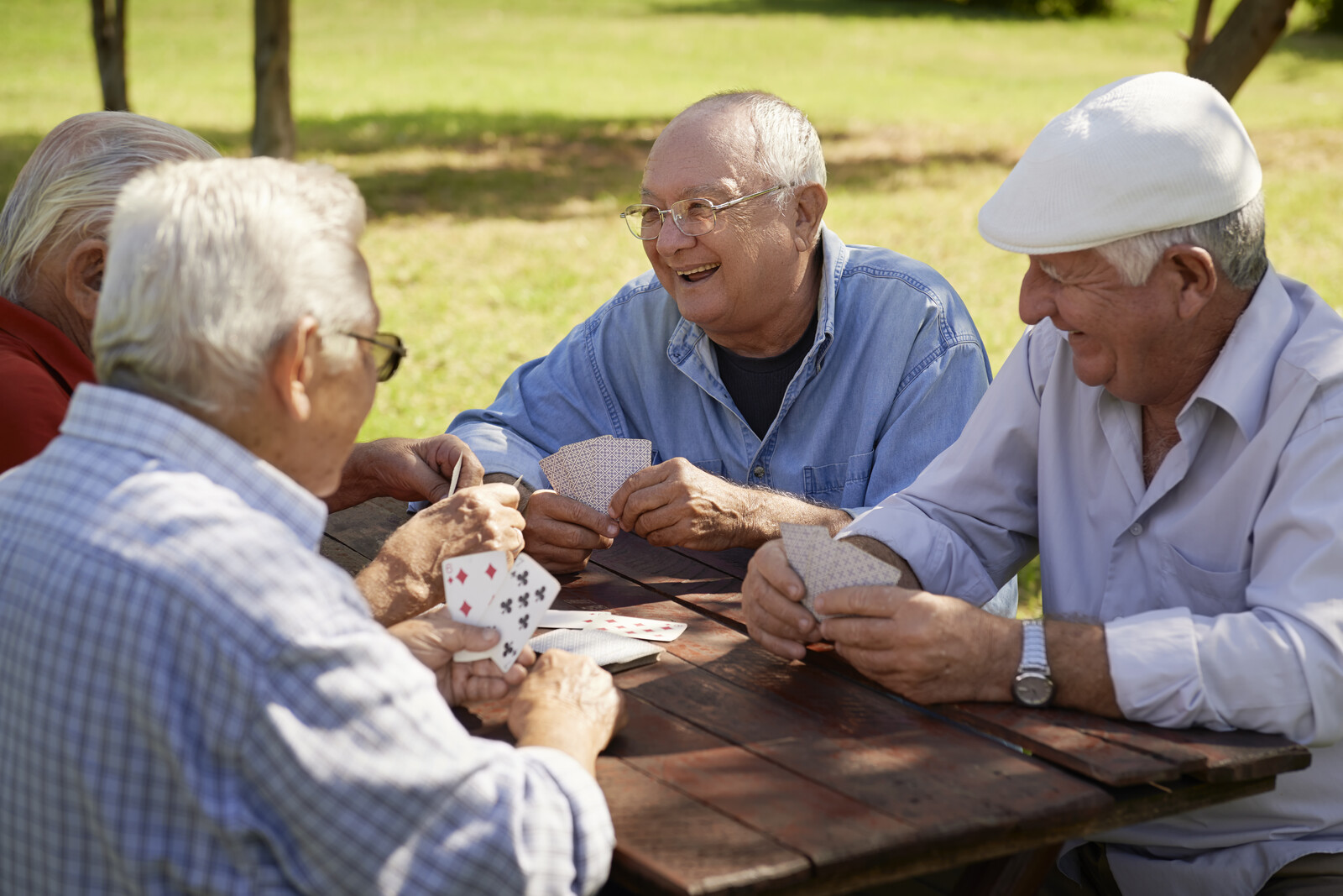 Four senior men sitting playing cards outside at a picnic table on a sunny day smiling and laughing