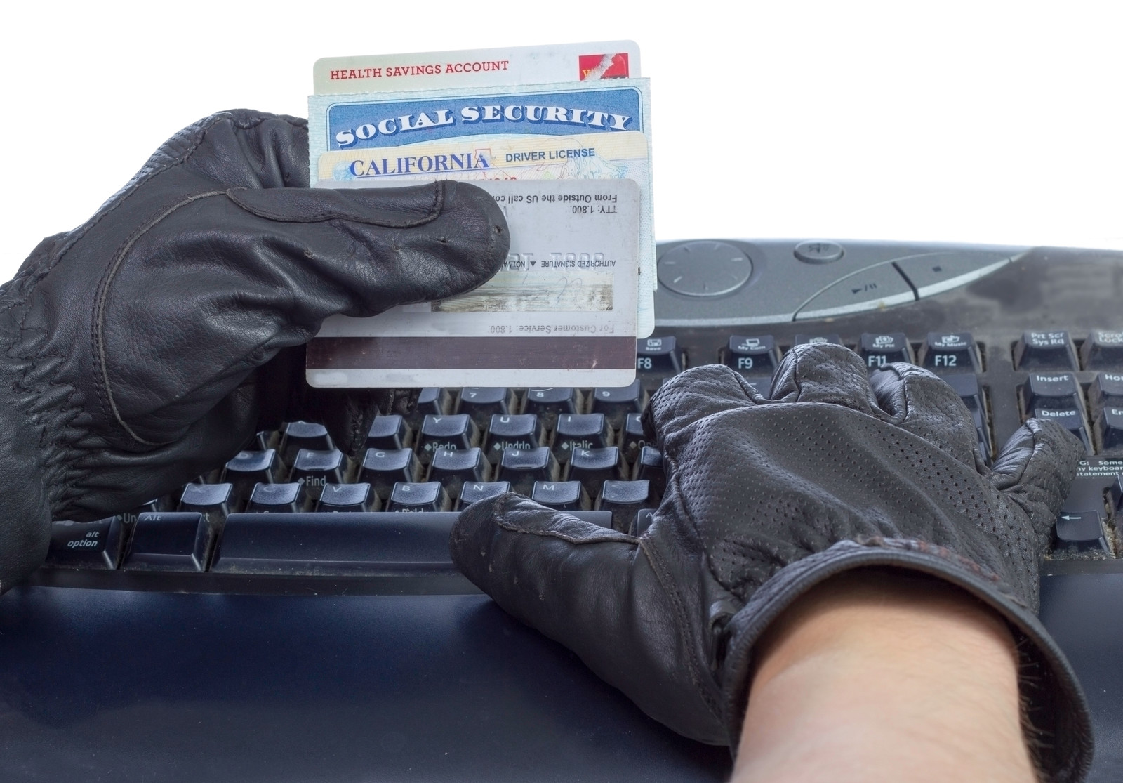 gloved hands typing on a computer holding stolen credit cards and social security card - photo represents identity theft