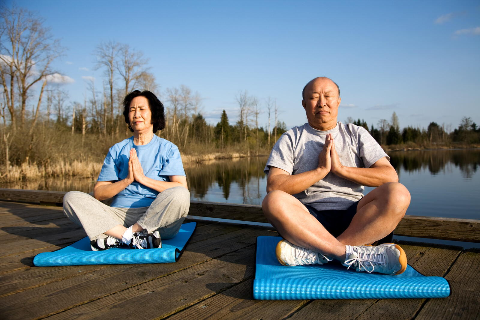 senior couple meditating on yoga mats outside on a dock on fall day with clear skies and calm water