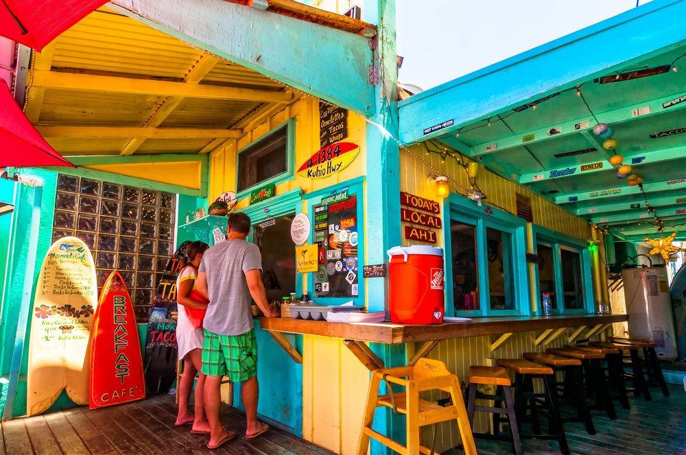 A brightly colored cafe in Kapaa, Kauai Hawaii where customers are standing to get their coffee order