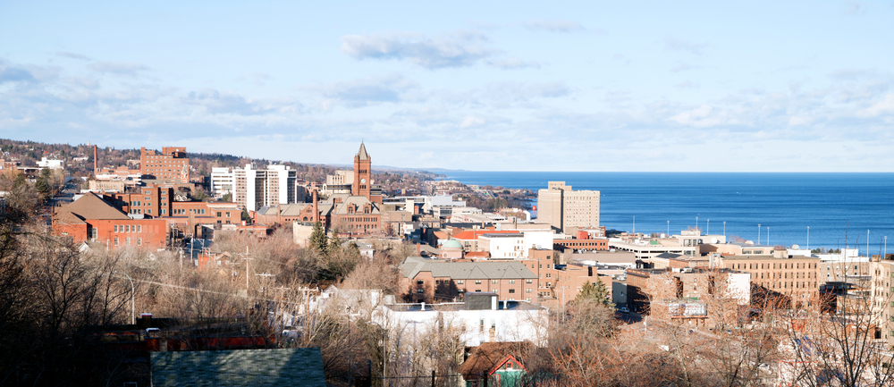 A city scene in Duluth Minnesota where the sky is light blue and the water can be seen too