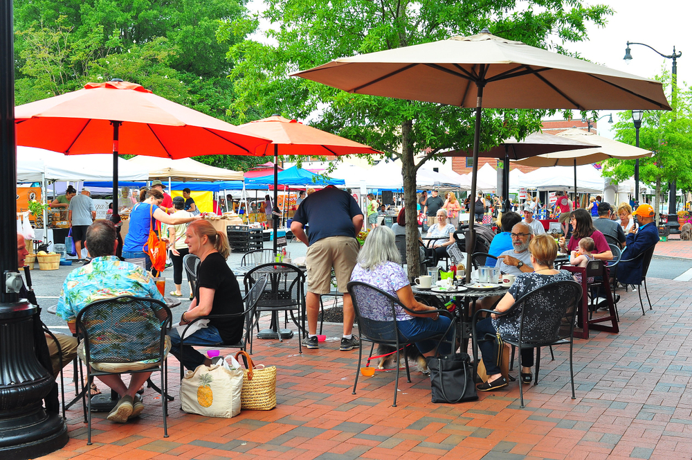 A farmer's market in Marietta City Georgia with customers sitting under red umbrellas
