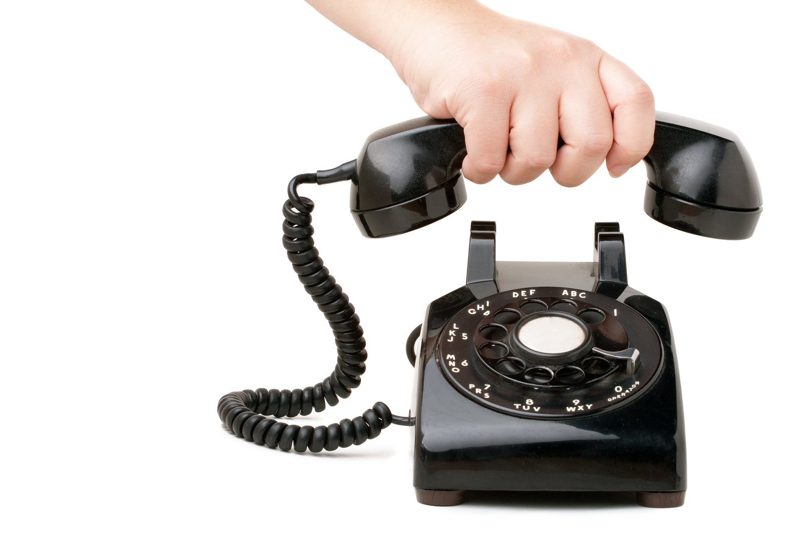 A hand hanging up a handset of an old black vintage rotary style telephone
