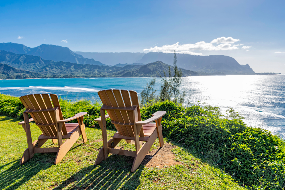 A pair of deck chairs overlooking the coast on Kauai Hawaii, where there are mountains in the background and sun is striking the water