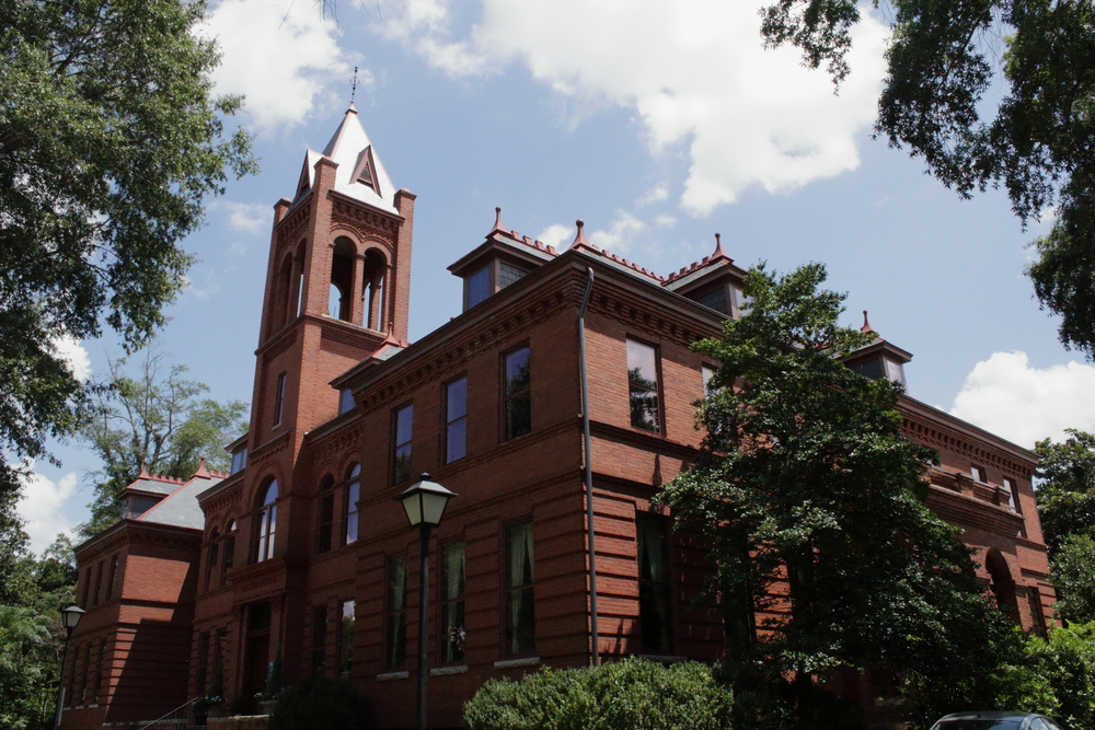 A red brick house in Madison Georgia the is partly in shadow and beneath a blue sky
