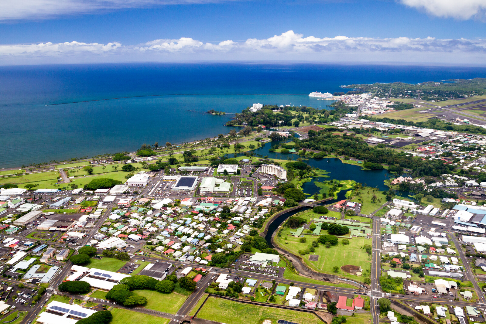 Arial view of Hilo city with green grass and trees with Bright blue skies melting into dark blue waters that turn turquiose closer to shore.